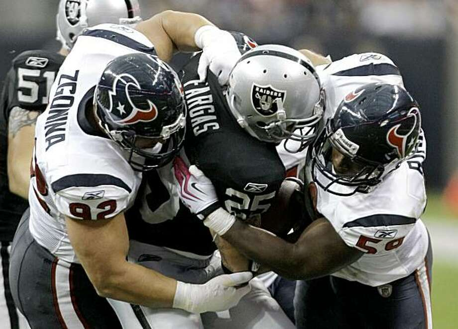 Houston Texans defensive tackle Jeff Zgonina (92) and linebacker DeMeco Ryans (59) stop Oakland Raiders running back Justin Fargas (25) for no gain during the 2nd quarter of an NFL football game at Reliant Stadium Sunday, Oct. 4, 2009, in Houston. The Texans beat the Raiders 29-6. Photo: Brett Coomer, Hearst Newspapers