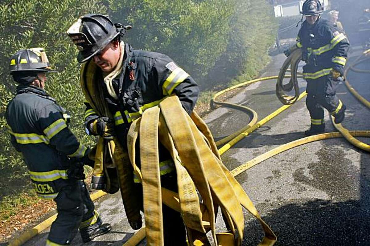 Marin County Firefighters Peter Falk (center) gathers up the hoses after cleaning up after a four alarm fire that broke out around 9:30 am at 116 Lyford Drive, Wednesday Oct. 21, 2009, in Tiburon, Calif.