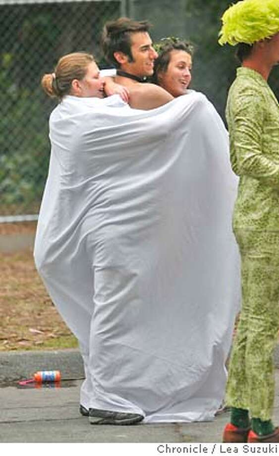 Melissa Bailey of Hazel Park, Michigan; Scott Kondak of Beverly Hills, Michigan and Emma Konkel of Milwaukee, Wisconsin huddle together under a sheet as they wait for the rest of their group during the 97th annual Bay to Breakers in 2008.  Photo: Lea Suzuki