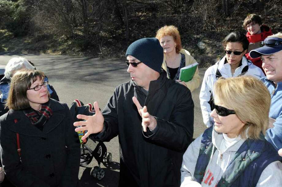 Greenwich resident, Thomas Agresta, center, makes a point to Melanie Bachman, left, staff attorney for the State of Connecticut Siting Council at the site of AT&T's proposed 17.5-foot concealed wireless tower, which would sit atop Aquarion Water Co.'s 48-foot water tower at 455 Valley Road, Cos Cob,Thursday, Feb. 9, 2012. The siting council, along with area residents, toured the proposed cell tower site Thursday. Agresta said that he lives across the Mianus River opposite the site. Photo: Bob Luckey / Greenwich Time