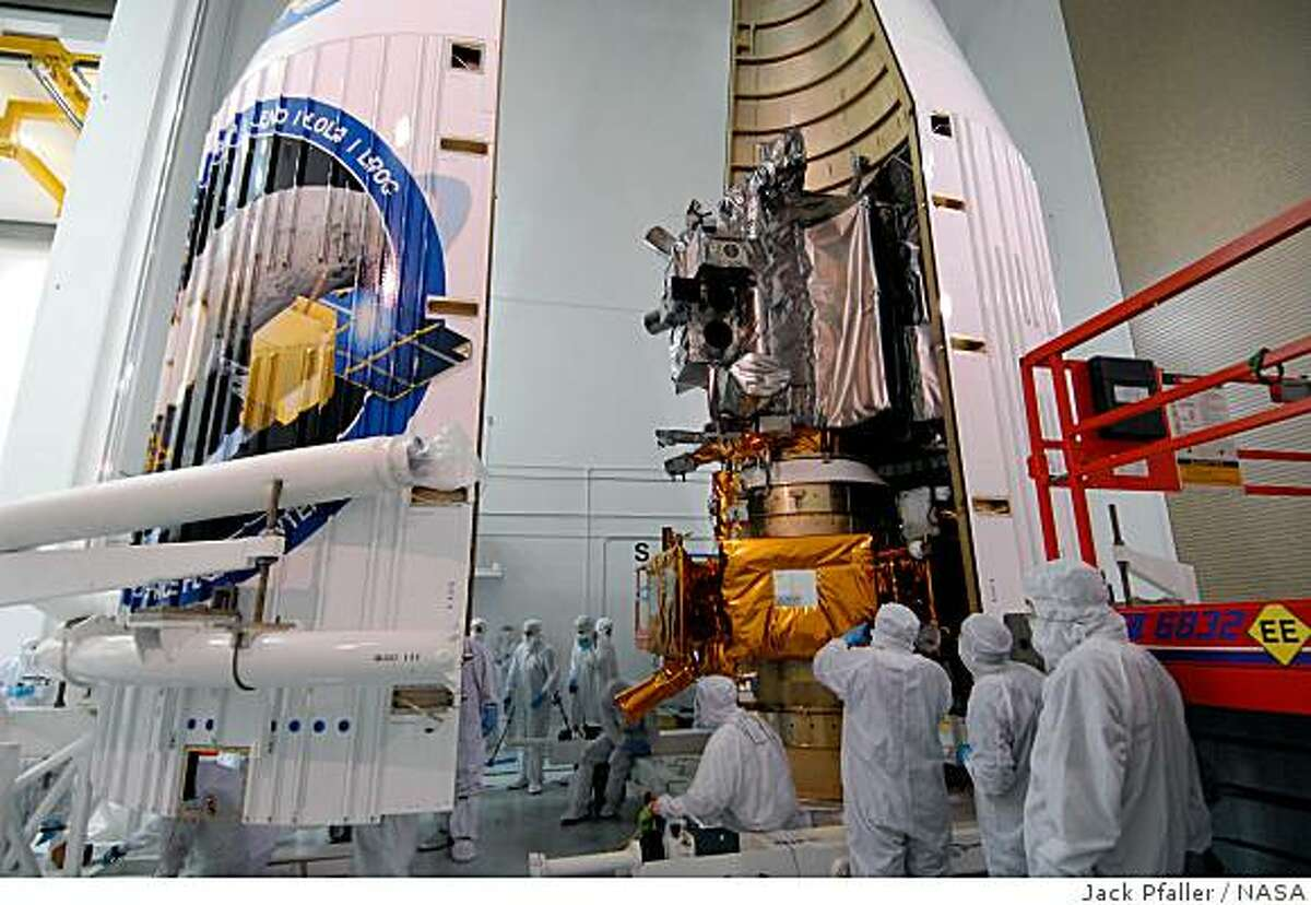 Technicians attempt to install NASA's Lunar Reconnaissance Orbiter, the LRO, and the Lunar Crater Observation and Sensing Satellite, the LCROSS, into a fairing at the Astrotech Space Operations Facility in Titusville, Fla., on May 15, 2009. The fairing is a molded structure that fits flush with the outside surface of the rocket and forms an aerodynamically smooth nose cone, protecting the spacecraft during launch and ascent.