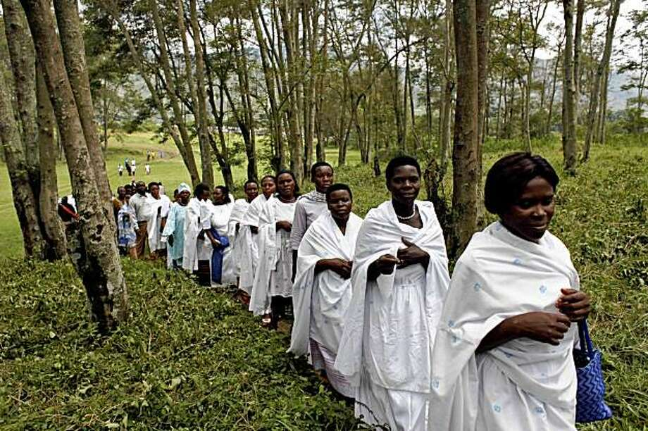 People walk through the woods to attend the coronation of Charles Wesley Mumbere as King of Rwenzururu in Kasese in western Uganda, Monday, Oct. 19, 2009. An African man who worked for years as a nurse's aide in the United States, caring for the elderly and sick, is back in his homeland after he was crowned king of his people in the mountains of western Uganda. (AP Photo/Karel Prinsloo) Photo: Karel Prinsloo, AP