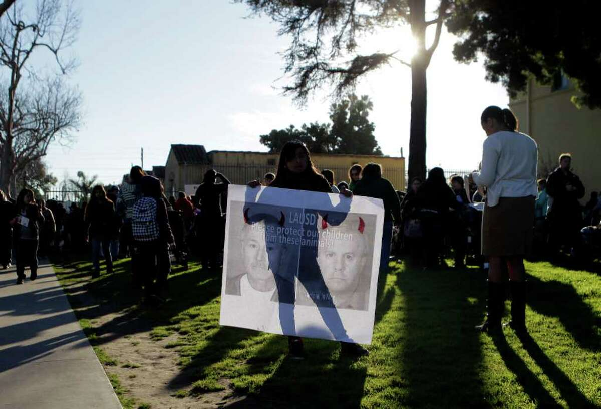 Nine-year-old Ashley Villatoro, center, holds a sign showing images of former teacher Martin B. Springer outside Miramonte Elementary School in Los Angeles, Thursday, Feb. 9, 2012.