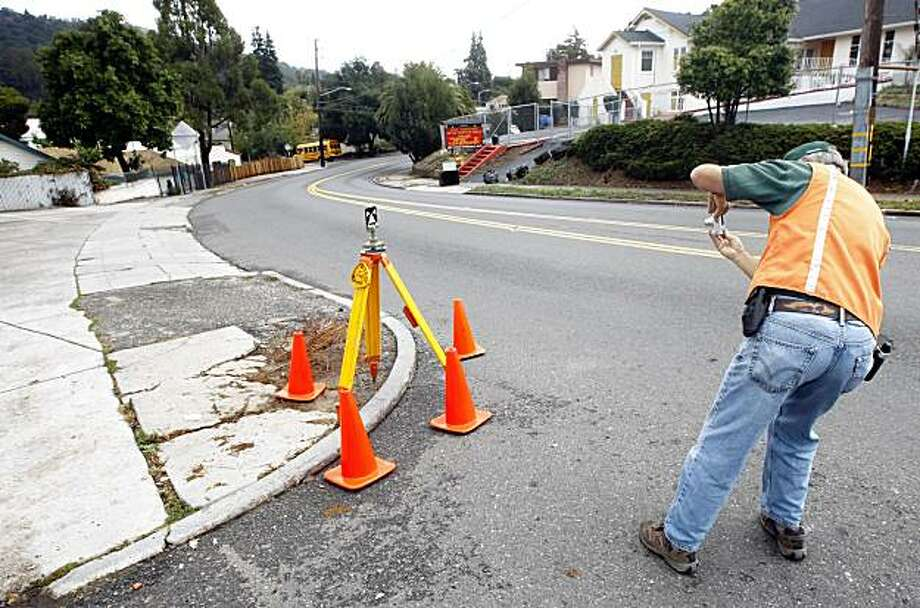 """US Geological survey scientists James J. Lienkaemper records the placement of his equipment after measuring the """"creep"""" along the Hayward Fault on Simpson Street in Oakland. Lienkaemper detected movement within a couple millimeters from the 2008 measurement. OnOct. 14, 2009the measurement was close to the Loma Prieta anniversary. Photo: Lance Iversen, The Chronicle"""