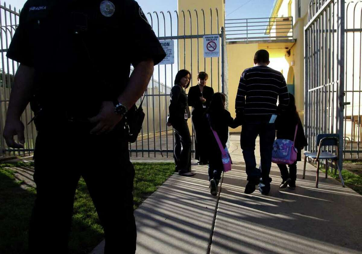 An adult accompanies two students into Miramonte Elementary School in Los Angeles on Thursday, Feb. 9, 2012. Children are returning to a Los Angeles-area elementary school where the entire staff has been replaced.