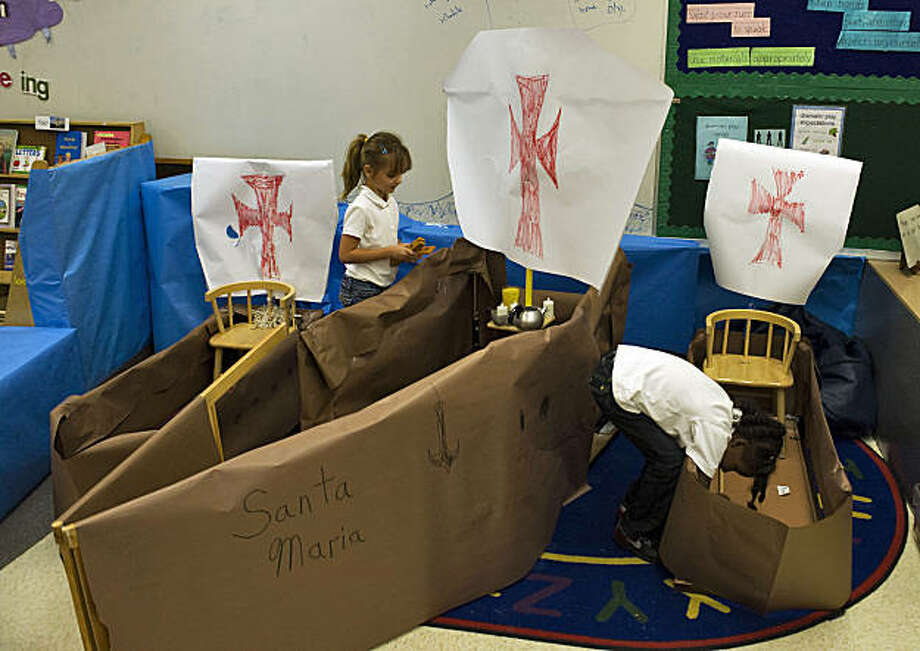 In this Oct. 9, 2009 photo, Kindergarten students Kaileen Barreto, left, and Shayonna Bridgeman  load supplies into a paper replicas of the ships Nina, Pinta and Santa Maria during a lesson about the voyage of Christopher Columbus to the New World at Philip Shore School of the Arts in Tampa, Fla.  Kolowith's students learn about the explorer's significance _ though they also come away with a more nuanced picture of Columbus than the noble discoverer often portrayed in pop culture and legend. Columbus' stature in U.S. classrooms has declined somewhat through the years, and many districts do not observe his namesake holiday. Although lessons vary, many teachers are trying to present a more balanced perspective of what happened after Columbus reached the Caribbean and the suffering of indigenous populations. (AP Photo/Steve Nesius) Photo: Steve Nesius, AP