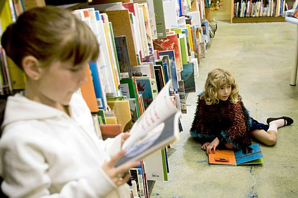 Anise Fernandez (left) and a friend check out the selection of children's books during the opening night party for the new Berkeley store of Books Inc., a locally owned independent bookstore chain, in Berkeley, Calif., on Thursday, October 8, 2009.