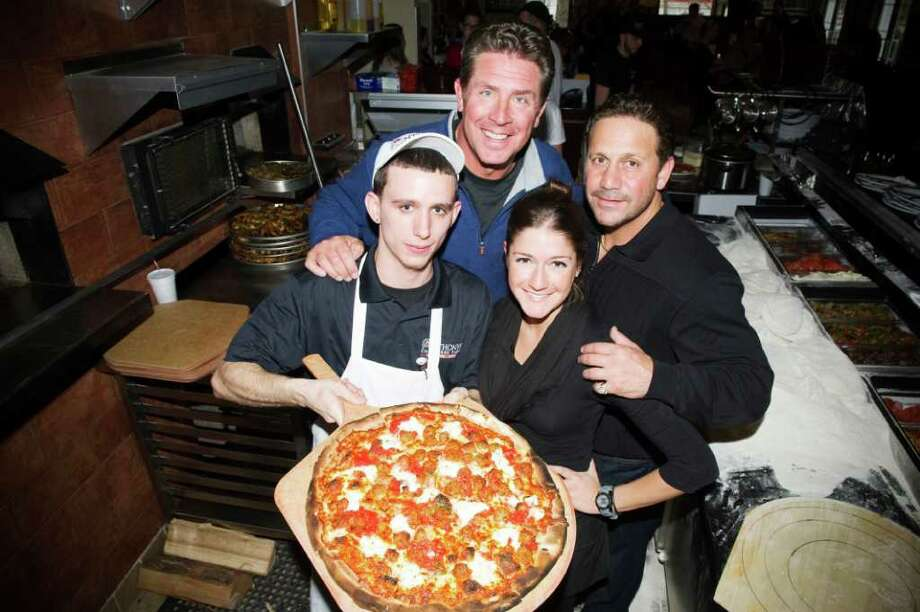 Retired Miami Dolphins quarterback Dan Marino poses with Anthony Bruno, right,, Shawn Kelly and Tara Bruno at Anthony's Coal Fired Pizza in Darien, Conn., February 8, 2012. Marino and Anthony Bruno have invested in the restaurant. Photo: Keelin Daly / Stamford Advocate