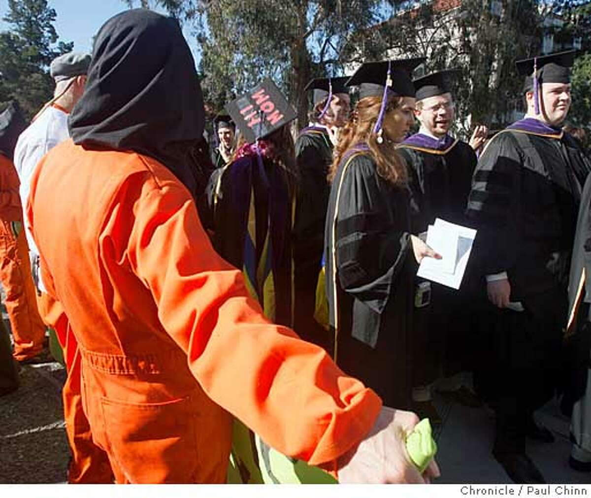 Boalt Law School graduates walk past anti-war protesters dressed as Guantanamo prisoners before graduation ceremonies in front of the Greek Theatre at UC Berkeley on Saturday, May 17, 2008. The demonstraters were denouncing law school professor John Yoo's participation in President Bush's terror policies. Photo by Paul Chinn / San Francisco Chronicle
