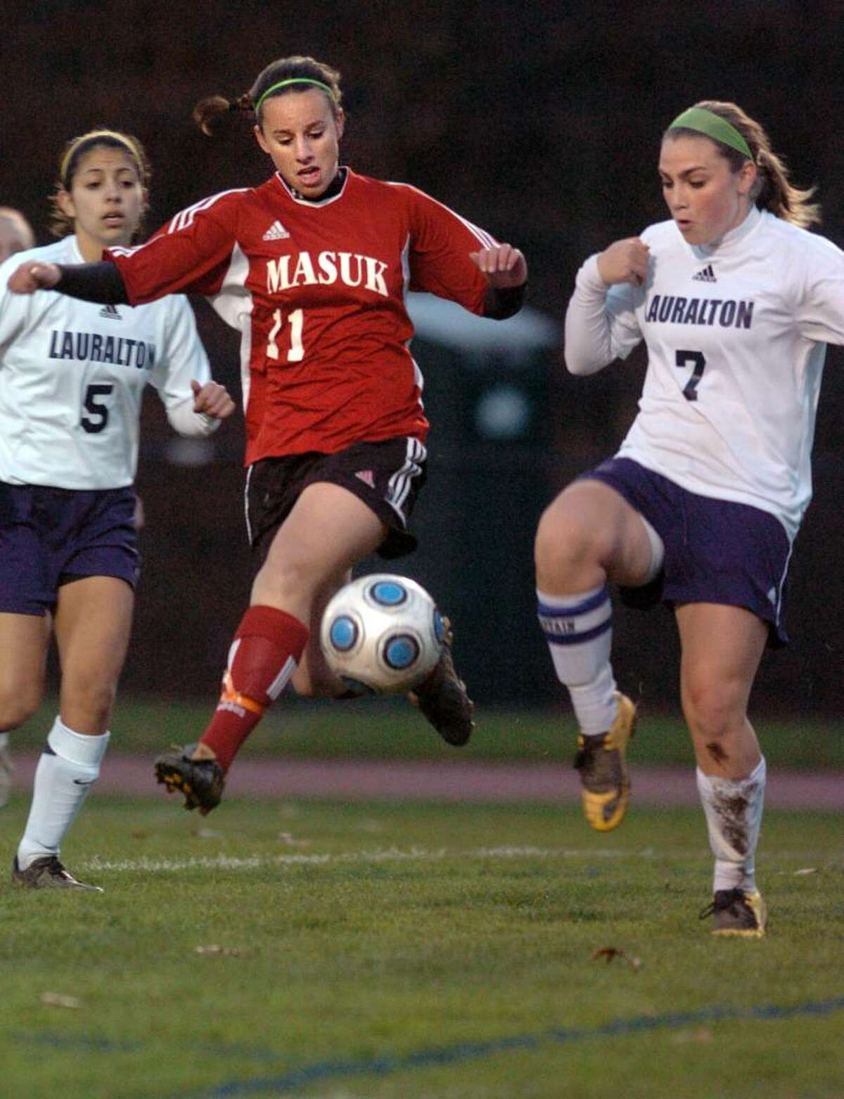 Masuk's Jackie McSally and Lauralton Hall's Taylor Healy go after the ball during the first half of Thursday night's South West Conference Girls Soccer Championship at Joel Barlow High School.