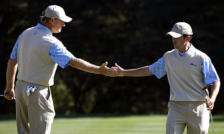 International player Ernie Els greets Mike Weir after Weir sank a birdie put on 13th putting his team one up on USA's Jim Furyk and Anthony Kim, in second rounds of the 2009 Presidents Cup played Harding Park in San Francisco California Friday Oct 9, 2009 Photo: Lance Iversen, The Chronicle