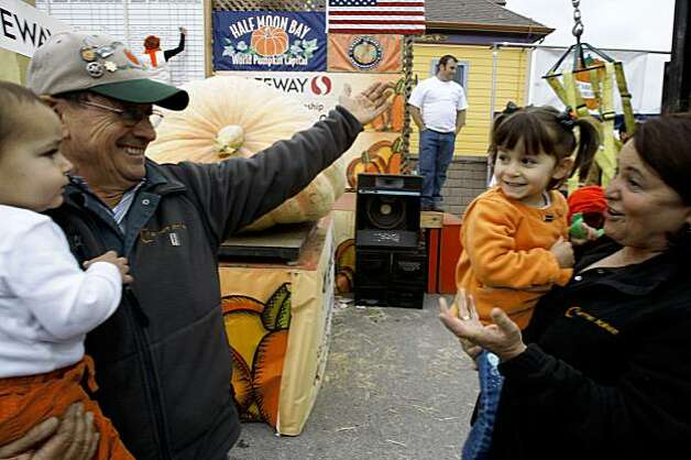Half Moon Bay Mayor Farmer John, left, with his grandson Lorenzo Bianchi, 16 months, lost by 13 pounds to his wife's pumpkin. Eda Muller, right, with granddaughter Delfina Bianchi, 4, at the 36th Annual Safeway World Championship Pumpkin Weigh-Off in Half Moon Bay on Monday. Muller entered a 1,200 pound pumpkin, the heaviest in the county. Photo: Liz Hafalia, The Chronicle
