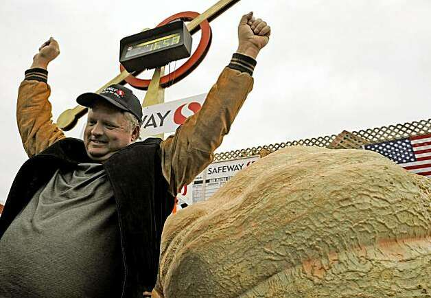Farmer Don Young, from Des Moines, Iowa, reacts next to his winning pumpkin at the Half Moon Bay 36th Annual Safeway World Championship Pumpkin Weigh-off in Half Moon Bay on Monday. Young's pumpkin weighed in at 1658 pounds, breaking the all previous records. Photo: Russel A. Daniels, AP