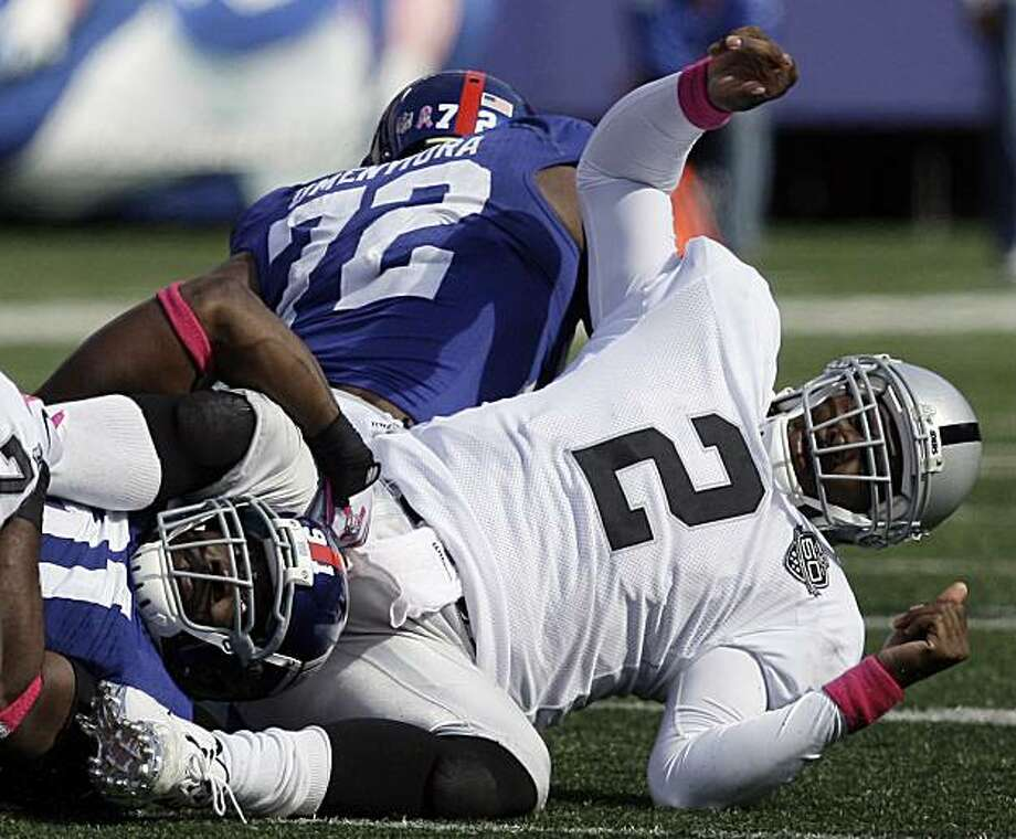 Oakland Raiders quarterback JaMarcus Russell (2) is sacked by New York Giants defensive end Justin Tuck, left, during the second quarter of an NFL football game, Sunday, Oct. 11, 2009, in East Rutherford, N.J. Russell fumbled the ball on the play which was recovered by Giants defensive end Osi Umenyiora. (AP Photo/Julie Jacobson) Photo: Julie Jacobson, AP