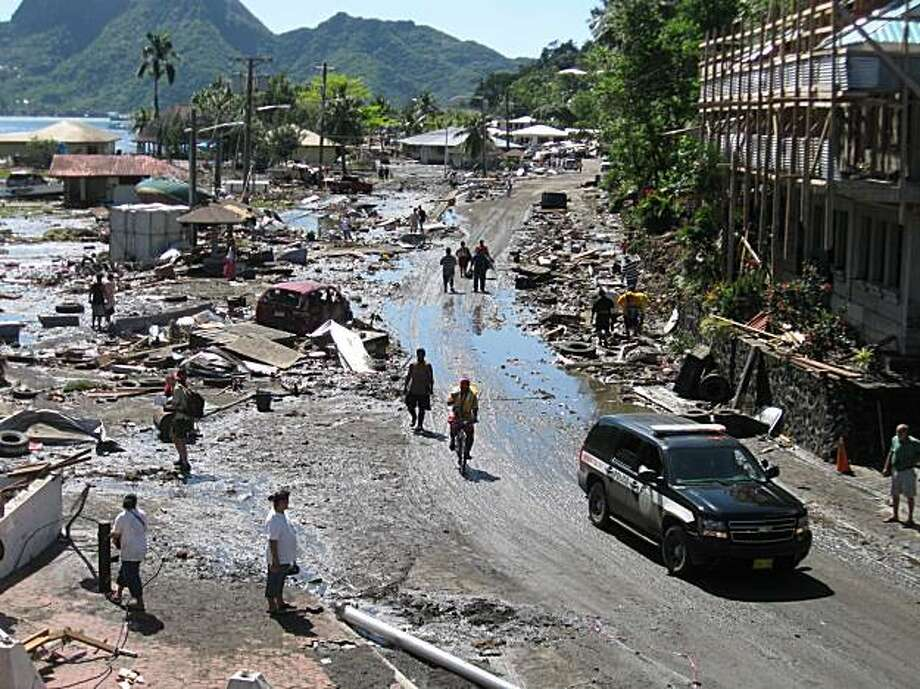 The scene of devastation in Pago Pago village, on American Samoa Wednesday, Sept. 30, 2009.  A powerful quake in the South Pacific hurled massive tsunami waves at the shores of Samoa and American Samoa, flattening villages and sweeping cars and people back out to sea while leaving many dead and dozens missing. AP Photo/Ausage Fausia) Photo: Ausage Fausia, Associated Press