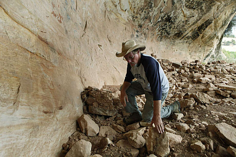 This Aug. 12, 2009 photo shows archaeologist Winston Hurst, 62,  looking over rocks in an ancient cliff dwelling west of Blanding, Utah. Hurst has become a champion of preservation, passionate about the need to leave pieces of the past in place. (AP Photo/Ed Andrieski) Photo: Ed Andrieski, AP