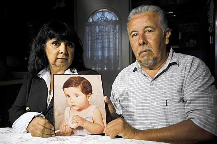This July 28, 2009 photo shows Virginia and Frank Zamora posing with a picture of their son, Dominic Zamora, an abuse victim who received a settlement from the Roman Catholic church, at their home near Los Angeles. The money was meant to soothe the victims' wounds and be a bridge to a better life, and for many it did. But for a few, the most deeply scarred, the six- and seven-figure checks have instead made things far worse. (AP Photo/Chris Carlson) Photo: Chris Carlson, AP