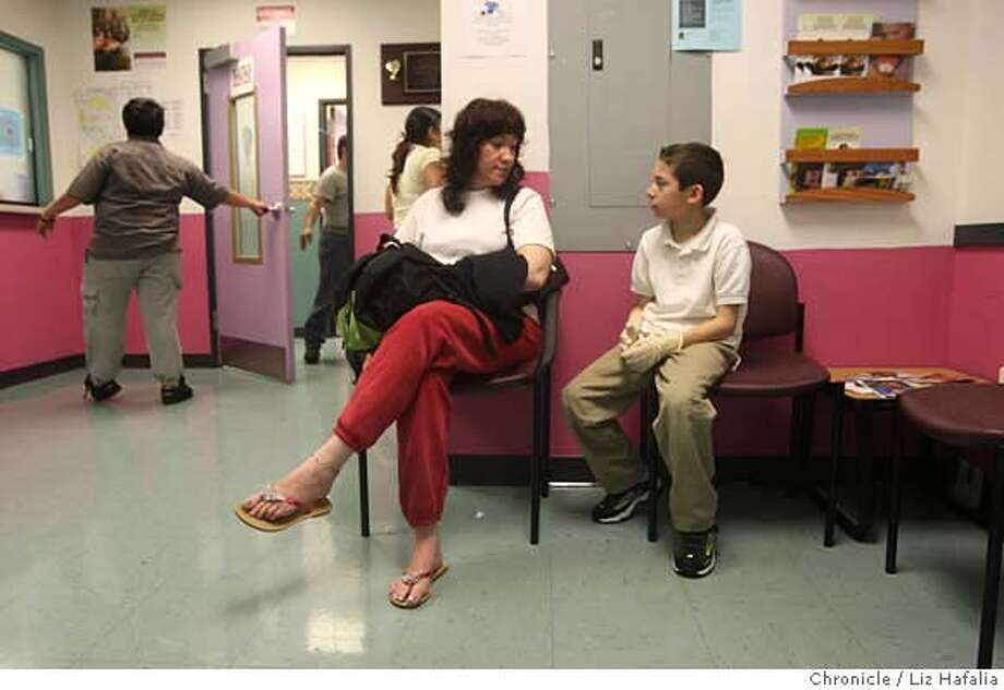 ###Live Caption:Raquel Cuellar and her eight-year-old son, Tadeo Cuellar, sit in the waiting room of the Mission Neighborhood Health Center in San Francisco, Calif., on May 13, 2008. Cuellar, who was waiting for her daughter, is concerned about how the latest revision in the budget cuts will affect her health care. Photo by Liz Hafalia / San Francisco Chronicle###Caption History:Raquel Cuellar and her eight-year-old son, Tadeo Cuellar, sit in the waiting room of the Mission Neighborhood Health Center in San Francisco, Calif., on May 13, 2008. Cuellar, who was waiting for her daughter, is concerned about how the latest revision in the budget cuts will affect her health care. Photo by Liz Hafalia / San Francisco Chronicle###Notes:Raquel Cuellar and her son Tadeo Cuellar, 8 years old, in the waiting room of Mission Neighborhood Health Center in San Francisco, Ca., as they wait for the daughter who is having a complete physical on Wednesday, May 13, 2008.  Liz Hafalia / The Chronicl###Special Instructions:MANDATORY CREDIT FOR PHOTOG AND SF CHRONICLE/NO SALES-MAGS OUT-INTERNET OUT-TV OUT Photo: Liz Hafalia