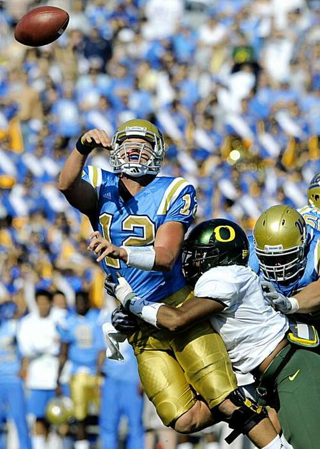 UCLA quarterback Richard Brehaut tries to get a pass off under pressure from Oregon linebacker Kenny Rowe during the second half of an NCAA college football game in Pasadena, Calif., Saturday, Oct. 10, 2009.  Oregon won 24-10. (AP Photo/Chris Carlson) Photo: Chris Carlson, AP