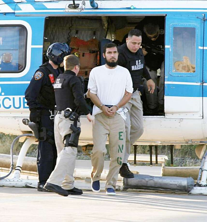 Najibullah Zazi, center, is escorted off an NYPD helicopter by U.S Marshals after being extradited from Denver, Colo., last Friday. Zazi was sent to New York to face charges of conspiracy to use weapons of mass destruction in a plot law enforcement has said was focused on blowing up commuter trains. Photo: NYPD, AP