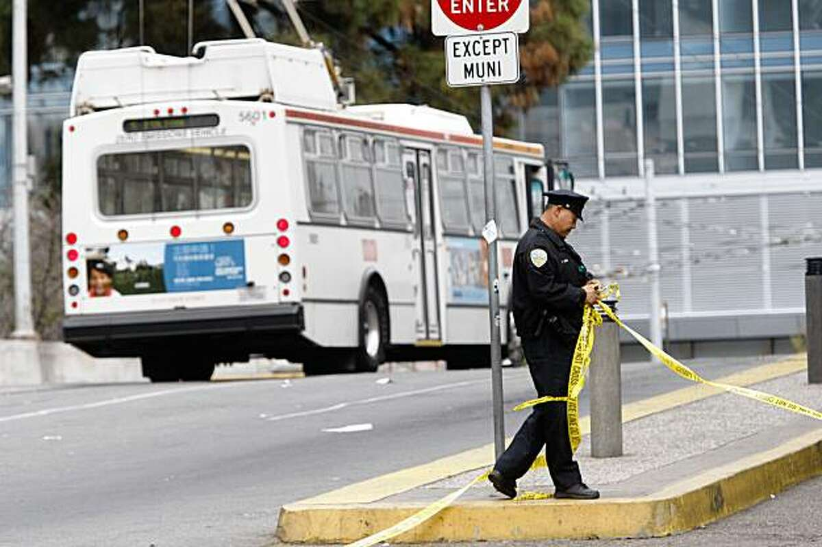 At the Transbay Terminal, San Francisco Police Officer Tedman Mark takes police tape down after the bus behind him was cleared from a bomb scare that happend earlier this morning when the bus drive found a suspicious bag on Monday Sep. 28, 2009 in San Francisco, Calif.