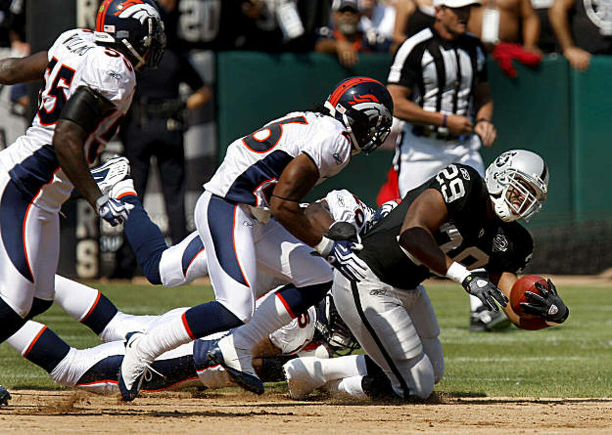 The Raiders Michael Bush is tackled for a short gain in the first quarter against the Broncos on Sunday.