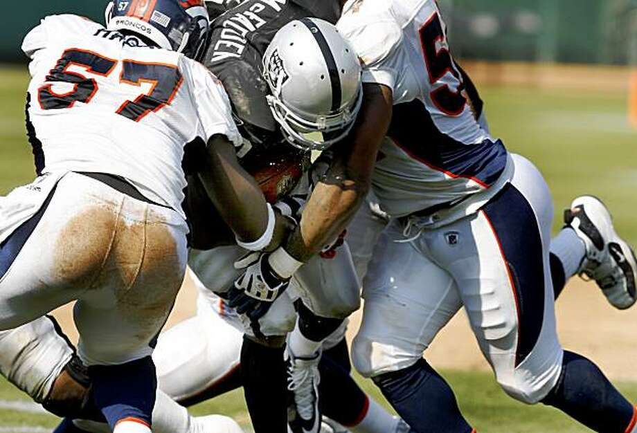 Darren McFadden is swarmed by Denver defenders for little gain on a 2nd half run. Oakland Raiders in action against the Denver Broncos Sunday September 27, 2009. The Raiders lost 23-3. Photo: Brant Ward, The Chronicle