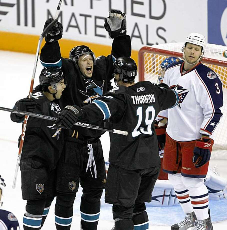San Jose Sharks right wing Dany Heatley, center, is congratulated by right wing Devin Setoguchi, left, and center Joe Thornton (19) after scoring past Columbus Blue Jackets defenseman Marc Methot (3) in the second period of an NHL hockey game in San Jose, Calif., Thursday, Oct. 8, 2009. (AP Photo/Paul Sakuma) Photo: Paul Sakuma, AP