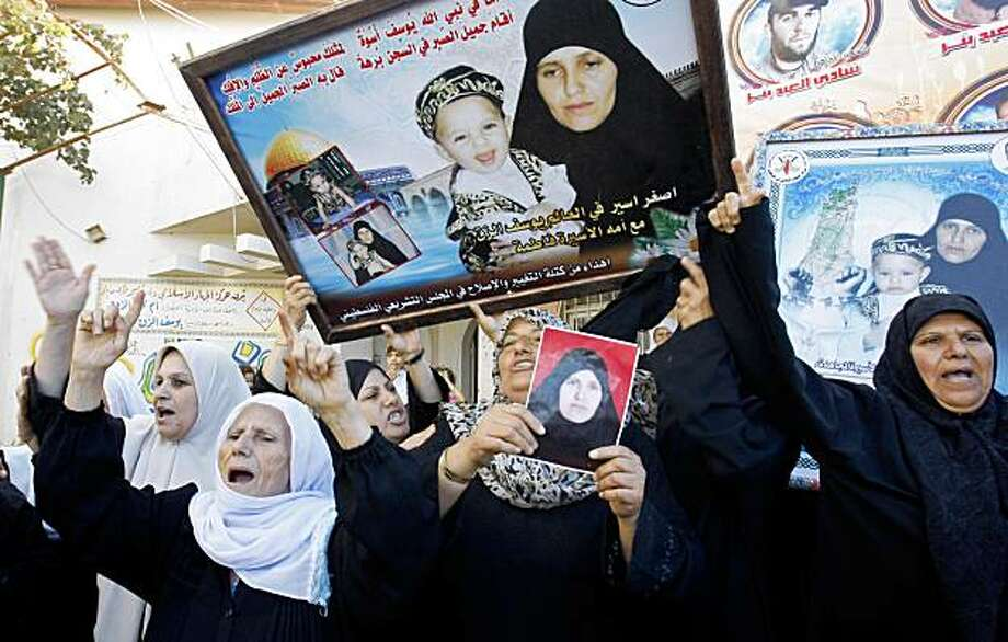 Palestinian relatives of Fatima  Al  Zaq, who is currently held in an Israeli prison and is on a list of prisoners scheduled to be released in the upcoming days, celebrate outside at the family  home in Gaza City, Wednesday, Sept. 30, 2009.  Israel will release 20 Palestinian women from prison this week in exchange for a videotape proving that Sgt. Gilad Schalit who is held by militants in the Gaza Strip is still alive, Israel and Hamas announced Wednesday, in the first tangible sign of movement in more than three years of talks over the captive soldier's fate. Schalit, a tank crewman seized by Hamas-linked militants in a cross-border raid in June 2006, has not been seen since his capture.(AP Photo/Hatem Moussa) Photo: Hatem Moussa, AP