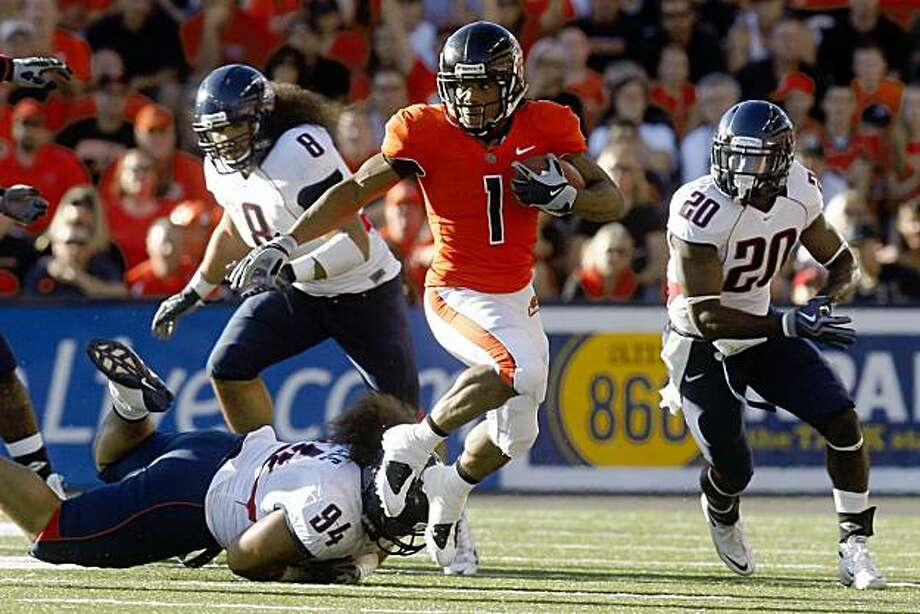 Oregon State's Jacquizz Rodgers runs from Arizona's  Lolomana Mikaele (94) while teammates Vuna Tuihalamaka (8) and Cam Nelson (20) look on during the first half of their NCAA college football game Saturday, Sept. 26, 2009, in Corvallis, Ore.  (AP Photo/Rick Bowmer) Photo: Rick Bowmer, AP