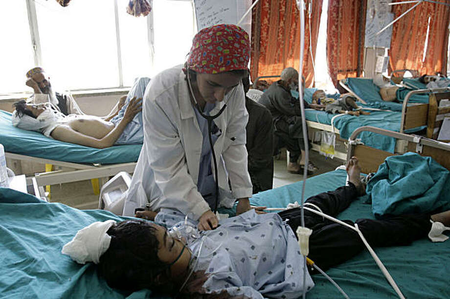 An Afghan woman doctor examines a girl passenger injured when a bus was hit by mine, as other victims are seen on the background at a hospital in Kandahar, Kandahar province, south of Kabul, Afghanistan on Tuesday, Sept. 29, 2009. Kandahar provincial police chief Sardar Mohammad Zazai said nine women and seven children are among the 30 killed in the blast. A packed bus traveling from the western city of Herat to Kandahar hit a land mine in Maiwand district Tuesday. Thirty-nine people were wounded. Photo: Allauddin Khan, AP