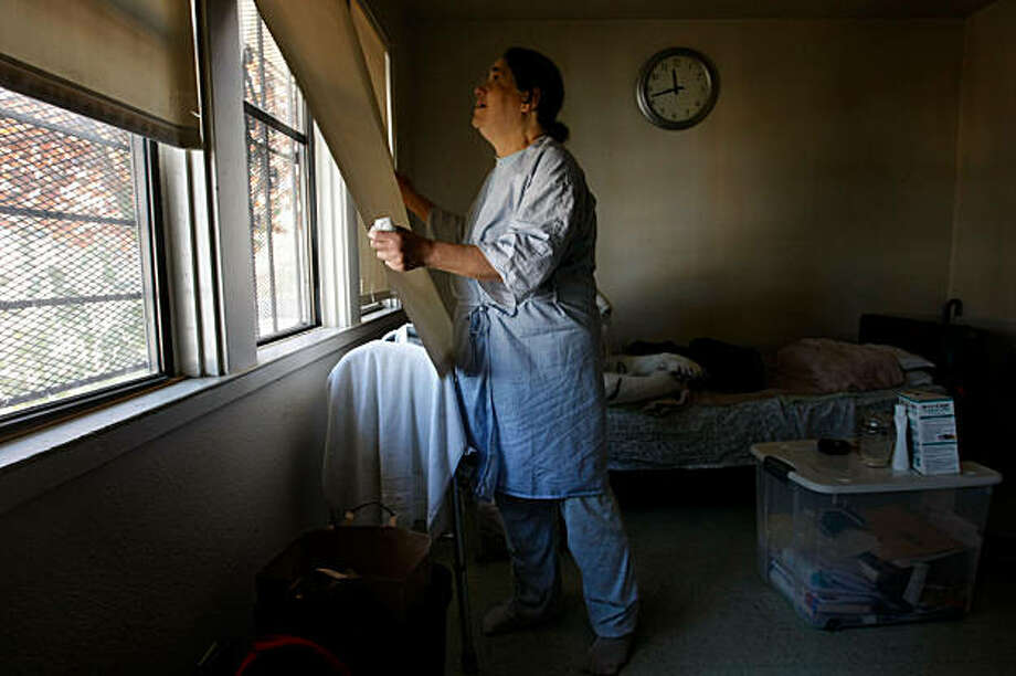 Carmen Windsor raises the window shades which are covered with bars in her apartment at Huntersview,  Thursday Oct. 8, 2009, in San Francisco, Calif. Photo: Lacy Atkins, The Chronicle