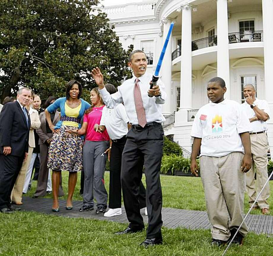 President Barack Obama uses a light saber as he watches a demonstration of fencing at an event supporting Chicago's 2016 host city Olympic bid, Wednesday, Sept. 16, 2009,  on the South Lawn of the White House in Washington. At rear is Chicago Mayor Richard Daley and first lady Michelle Obama. (AP Photo/Charles Dharapak) Photo: Charles Dharapak, AP
