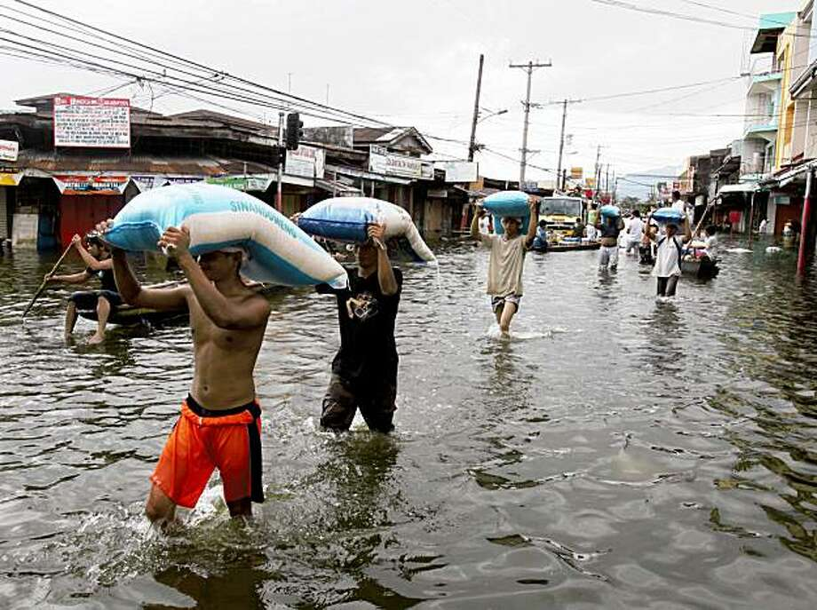 Workers carry sacks of rice for stocking to dry warehouse as residents go on their daily business amidst flooding at Santa Cruz township, Laguna province south of Manila, Philippines for more than a week Sunday Oct. 4, 2009. Tropical storm Ketsana brought the worst flooding in metropolitan Manila and neighboring provinces in more than 40 years.  (AP Photo/Bullit Marquez) Photo: Bullit Marquez, AP
