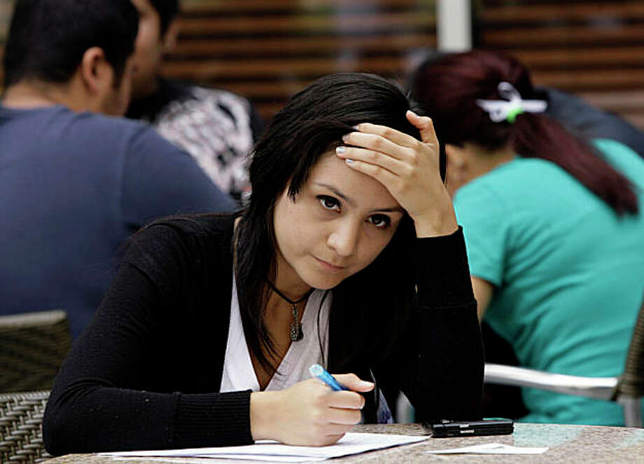 Avelica Rubio pauses while filling out a job application at the Anaheim Orange County Fair and Expo, Wednesday, June 3, 2009 in Anaheim, Calif. The number of people on the unemployment insurance rolls fell slightly for the first time in 20 weeks, while the tally of new jobless claims also dipped, the government said Thursday. (AP Photo/Nick Ut) Photo: Nick Ut, AP / ONLINE_CHECK