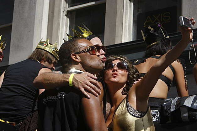 A group takes a self-portrait as LovEvolution makes its way down Market Street to Civic Center Plaza in San Francisco on Saturday. Photo: Frederic Larson, The Chronicle