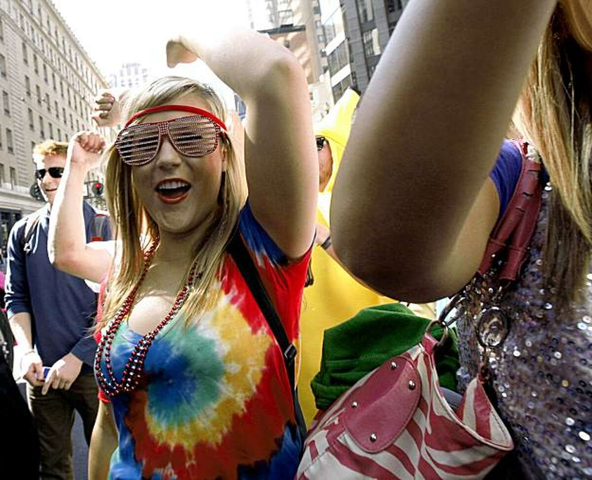 People dance and party along the parade route as LovEvolution makes its way down Market Street to Civic Center Plaza in San Francisco on Saturday.