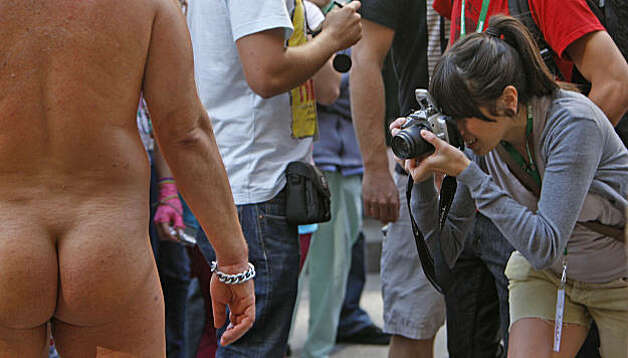 A photographer takes a close-up of a naked man as LovEvolution makes its way down Market Street to Civic Center Plaza in San Francisco on Saturday. Photo: Frederic Larson, The Chronicle
