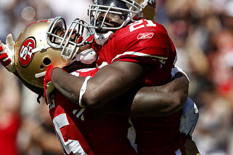Frank Gore (top) is celebrates with Vernon Davis after Gore's touchdown in the first half of the 49ers home opener against the Seattle Seahawks on Sunday. Photo: Brant Ward, The Chronicle