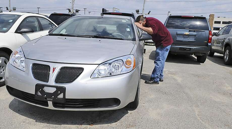 Matt Aquano, of Danvers, Mass., looks at a Pontiac G6, that he is planning to purchase when he trades in his Chevy Trailblazer, at a car dealership, Thursday, May 1, 2008 in Danvers, Mass. Behind are sport utility vehicles that were traded in at the dealership. Aquano stated that he is trading in his SUV for a 4-cylinder car for better gas mileage. General Motors Corp. said its truck and SUV sales were down 27 percent, dragging down increases in car and crossover sales. GM's overall sales were down 16 percent for the month compared with last April. (AP Photo/Lisa Poole) Photo: Lisa Poole, AP