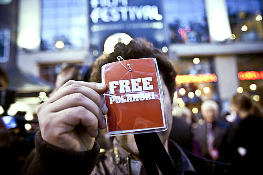 "A man holds a ""Free Polanski"" sticker as he waits at the film festival in Zurich, Switzerland, Sunday Sept. 27, 2009. Director Roman Polanski was arrested by Swiss police as he flew in for the Zurich Film Festival and faces possible extradition to the United States for having sex with a 13-year-old girl in 1977, authorities said Sunday.(AP Photo/Keystone, Ennio Leanza) Photo: Ennio Leanza, AP"
