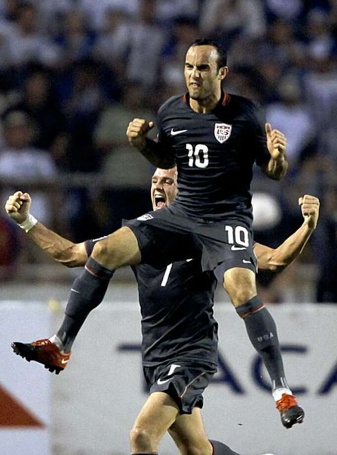 U.S. Landon Donovan, top, celebrates with teammate Stuart Holden after scoring against Honduras during a 2010 World Cup qualifying soccer match in San Pedro Sula, Honduras, Saturday Oct. 10, 2009. U.S. won 3-2 and classified for the 2010 World Cup. (AP Photo/Claudio Cruz) Photo: Claudio Cruz, AP