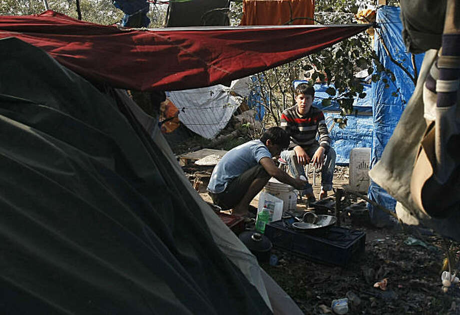 "Migrants wash their dishes in a bucket at the so-called ""jungle""camp in Calais, northern France, Saturday, Sept. 19, 2009. The camp in the French port city of Calais, used by migrants waiting to cross into Britain from France, is to be closed and demolished, French officials have announced. The camp was established after the official Red Cross camp at Sangatte near Calais was closed in 2002. It is estimated some 1500 people live at the camp which is known locally as 'the jungle'. French officials have said each one of the residents at the camp would be given the chance to apply for asylum or be repatriated. (AP Photo/Michel Spingler) Photo: Michel Spingler, AP"