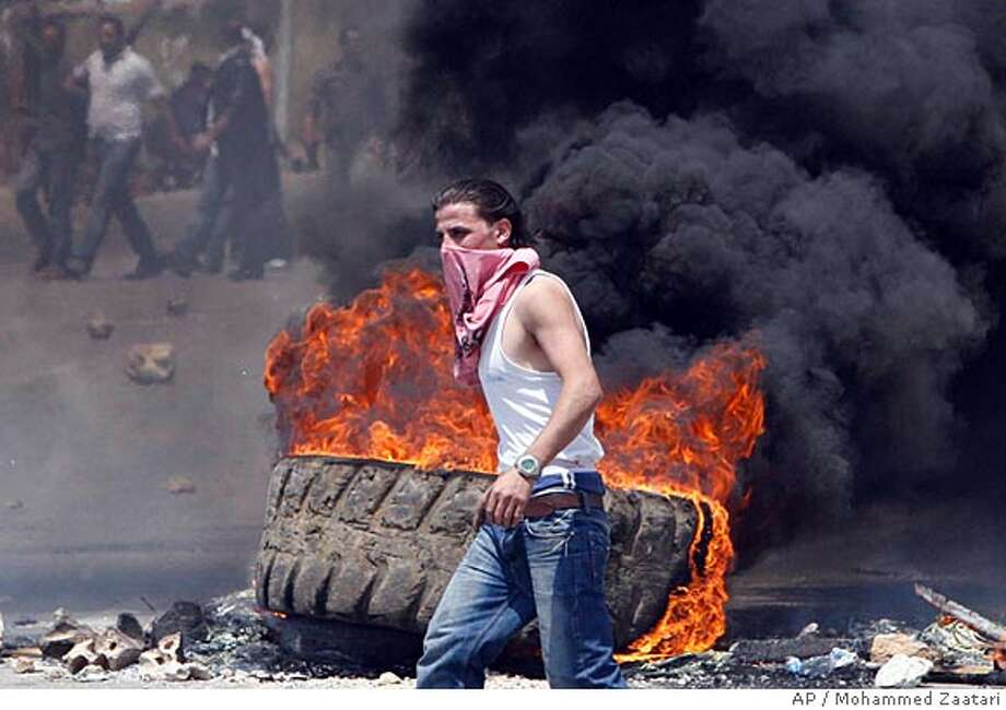 A Sunni supporter of parliamentary majority leader Saad Hariri burns tires to block the highway linking Beirut with coastal village of Jiyeh, Lebanon, Thursday, May 8, 2008. Shiite supporters of Iranian-backed Hezbollah and Sunnis backing Lebanon's U.S.-allied government clashed for a second day Thursday as sectarian confrontations in Beirut spilled over to other parts of the country. (AP Photo/Mohammed Zaatari) Photo: Mohammed Zaatari