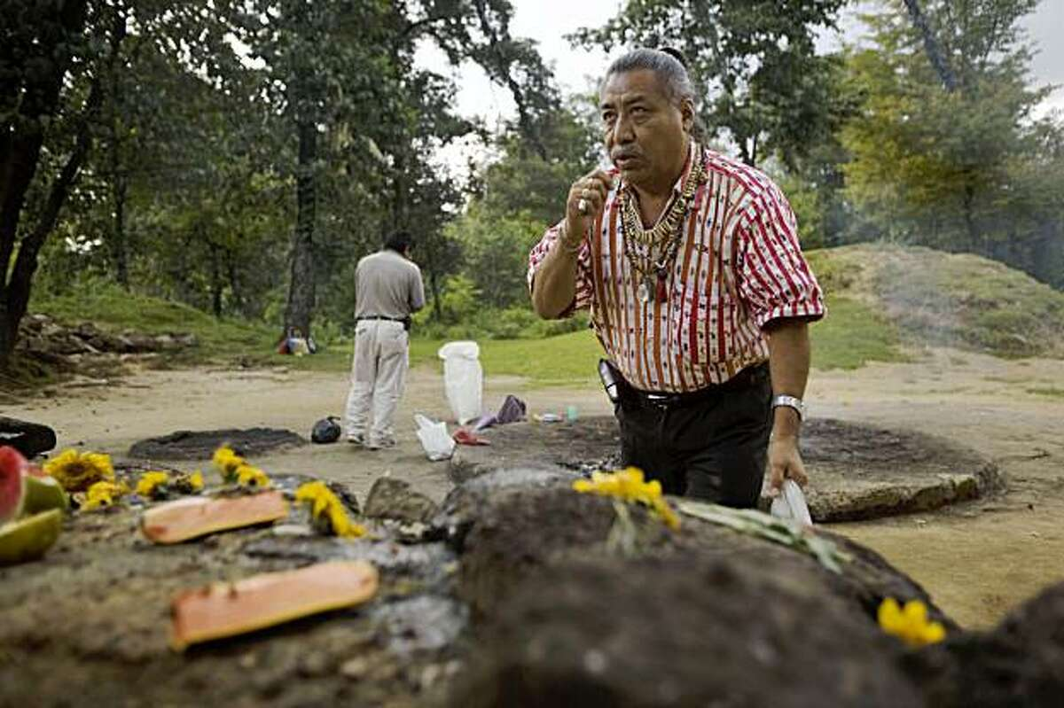 """**ADVANCE FOR SUNDAY, OCT. 11** In this photo taken Oct. 3, 2009, Guatemalan Mayan Indian elder Apolinario Chile Pixtun gestures as he pays his respects at an altar within the Iximche ceremonial site in Tecpan, Guatemala. Archaeologists, astronomers and modern-day Mayas shrug off the popular frenzy over the date of 2012, predicting it will bring nothing more than a meteor shower of new-age """"consciousness,"""" pseudo-science and alarmist television specials. (AP Photo/Moises Castillo)"""