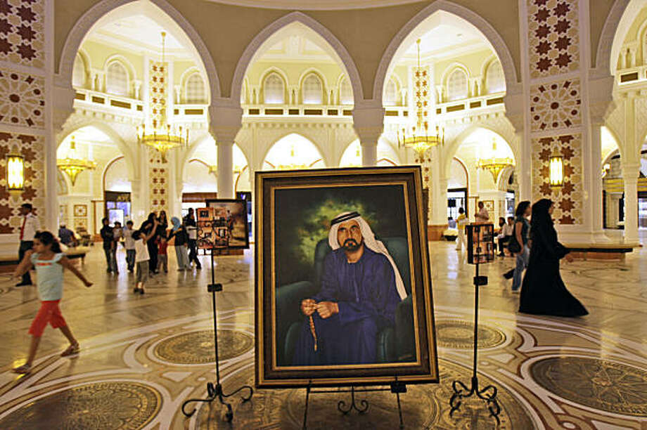 In this photo taken Thursday, July 30, 2009, a painting of Sheik Mohammed Bin Rashid Al Maktoum, UAE Prime Minister and Ruler of Dubai is seen at a shopping mall in Dubai, United Arab Emirates. Until recently, Dubai's ruler was the envy of the capitalist world. As he prepares to pitch his indebted emirate to the recession-stricken investors at the much anticipated property fair, it's unlikely Mideast's most ambitious leader will succeed in reclaiming any of the boom-time glory for his Gulf fiefdom. (AP Photo/Kamran Jebreili) Photo: Kamran Jebreili, AP