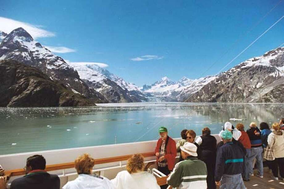 TRAVEL CRUISE -- Cruise passengers sailing in the Johns Hopkins Inlet in Alaska.  (PHOTO BY SPUD HILTON / THE CHRONICLE: JULY 2001) Passengers on an Alaskan cruise view the dramatic scenery of the Johns Hopkins Inlet. ALSO Ran on: 04-09-2006  Peaks jut from Johns Hopkins Inlet in Glacier Bay. Many cruise passengers who discover Alaska's scenery by sea will return by land. Photo: Spud Hilton