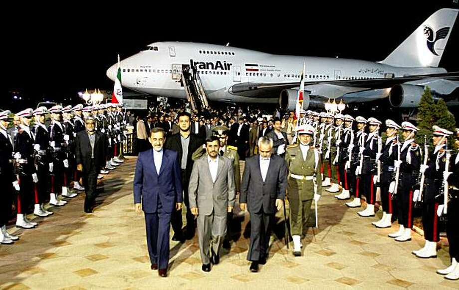 "Iranian President Mahmoud Ahmadinejad (C) is welcomed by officials at Tehran's Mehrabad Airport on September 26, 2009 upon his return from the UN General Assembly meeting in New York. Ahmadinejad said upon his return that the disclosure of Iran's new uranium enrichment plant was a ""firm blow"" to Western powers opposed to Tehran's atomic work, the ILNA news agency reported. AFP PHOTO/ATTA KENARE (Photo credit should read ATTA KENARE/AFP/Getty Images) Photo: Atta Kenare, AFP/Getty Images"