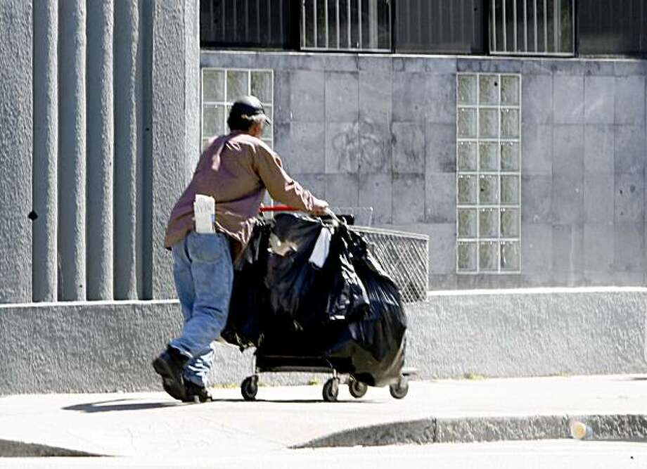 After rummaging through a garbage can, a man pushes his shopping cart on 9th Street, on Wednesday April 16, 2008, in San Francisco, Calif. Photo by Katy Raddatz /  San Francisco Chronicle Photo: KATY RADDATZ, SFC