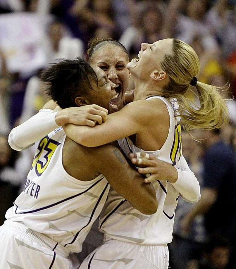 Phoenix Mercury's Cappie Pondexter, left, Diana Taurasi, second left, and Penny Taylor, right, from Australia, celebrate a win over the Indiana Fever in the closing moments of the fourth quarter of Game 5 of the WNBA basketball finals Friday, Oct. 9, 2009, in Phoenix. The Mercury defeated the Fever 94-86 to win the WNBA championship. (AP Photo/Ross D. Franklin) Photo: Ross D. Franklin, AP